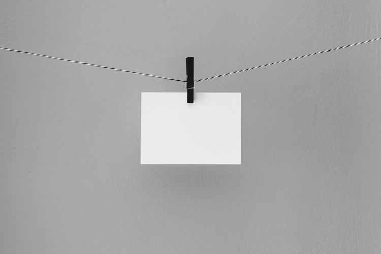 Blank envelope hanging on a sting, held by a clothesline pin