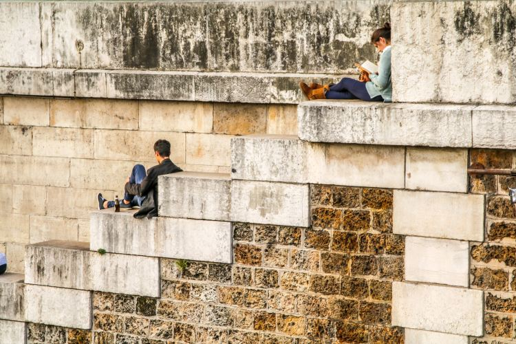 Two people reading against a brick wall