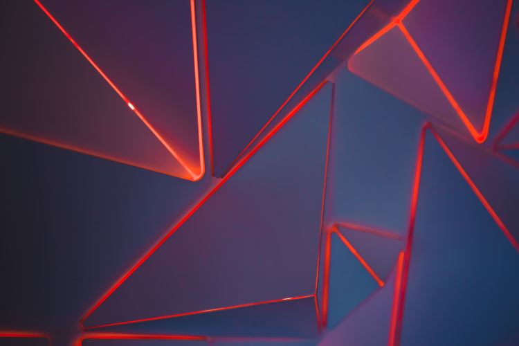Geometric image of red neon triangles on a slate background