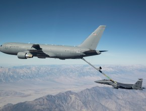 aerial tanker refueling a fighter jet above the mountains