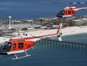 two helicopters flying over a beach
