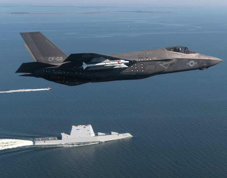 A fighter jet carrier missiles flies over a navy destroyer