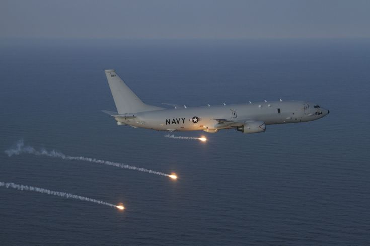 a military aircraft drops flares over the ocean