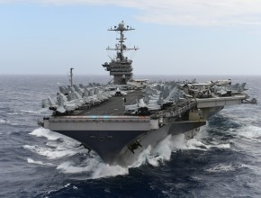an aircraft carrier with jets on the flight deck