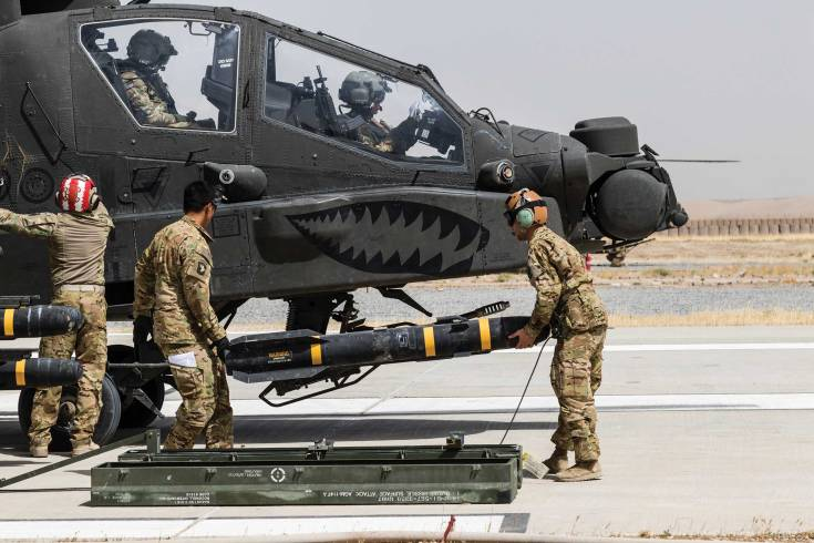 army soldiers carrying a missile in front of a helicopter
