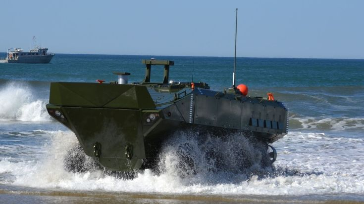 wheeled military vehicle driving out of the water onto a beach