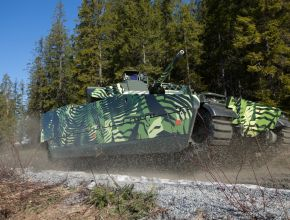 tracked combat vehicle driving offroad near a forrest