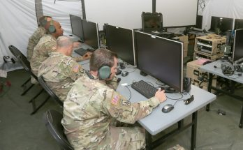 Soldiers working on computers in a tent