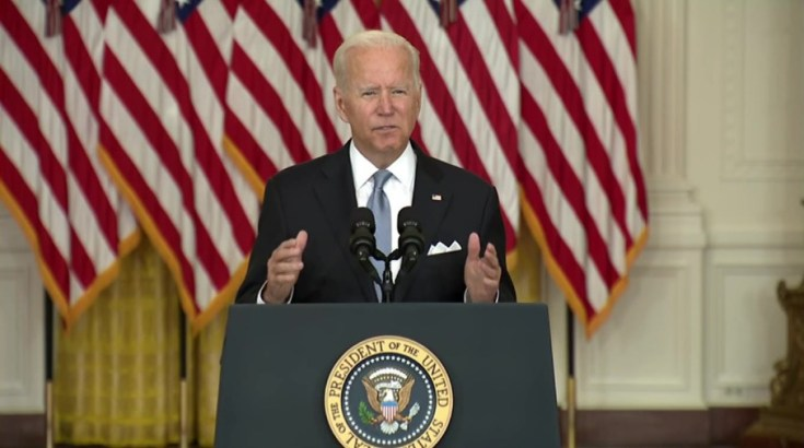 President Joe Biden standing at a podium in front of American flags