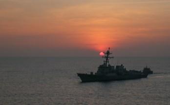 A u.s. navy warship sails at sunset