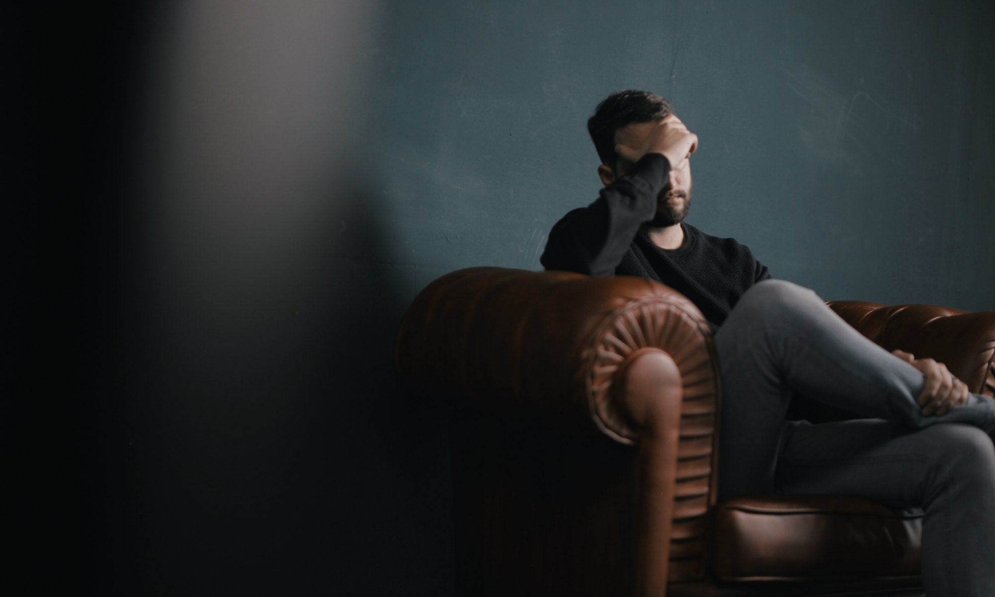 Man sitting on couch with hand on forehead worried and stressed