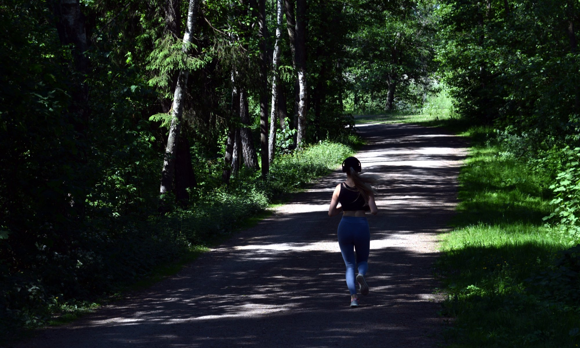 Woman with headphones jogging in nature on forest trail near green trees