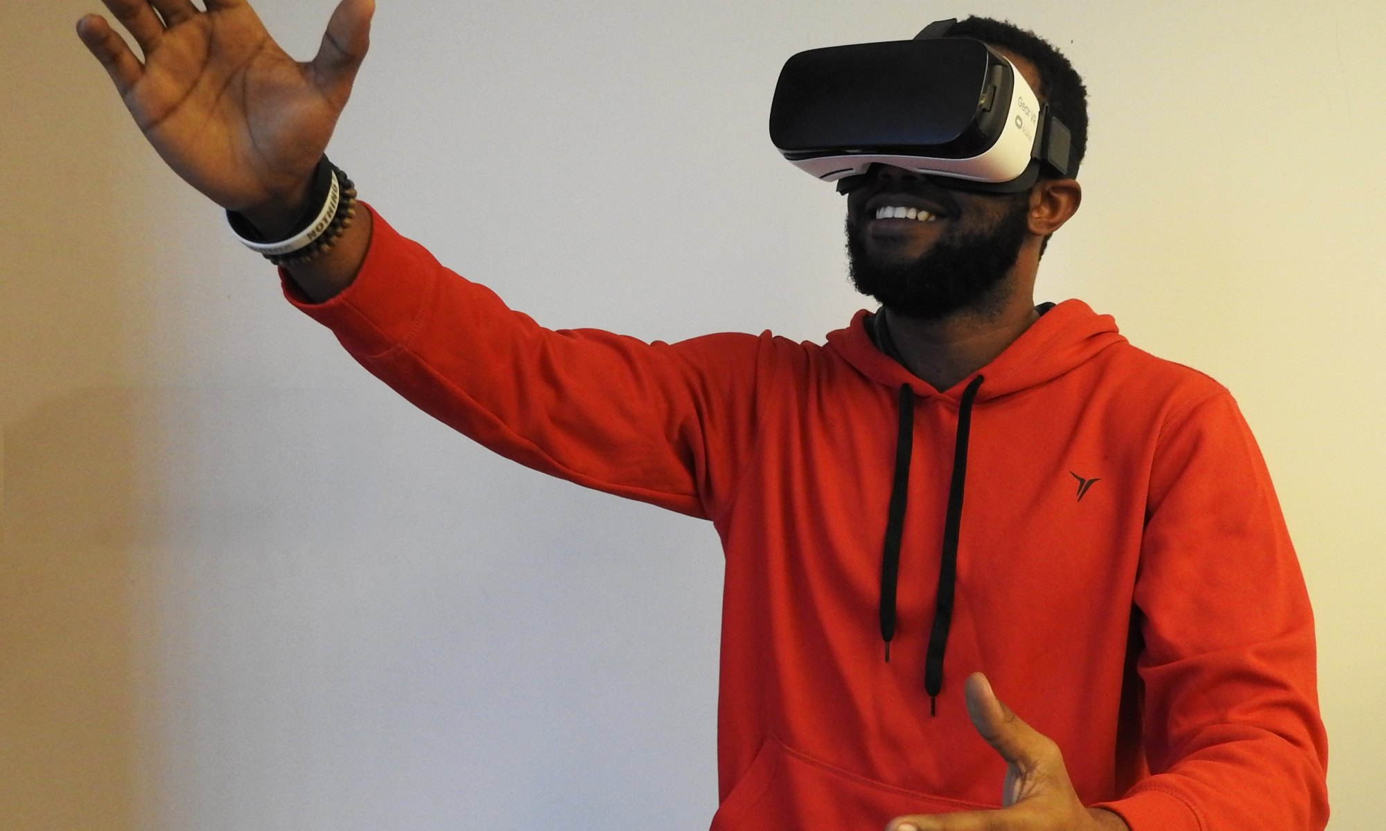 Black man in orange hoodie wearing white VR headset accepting his reality while lifting right hand