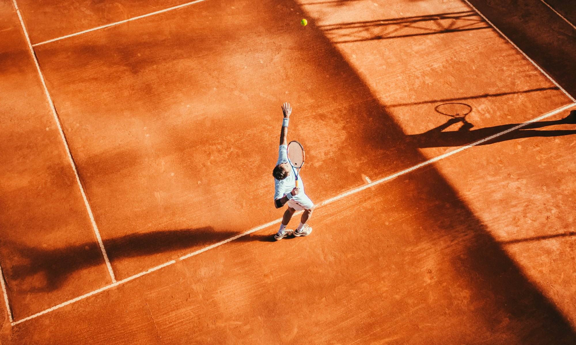 Man playing tennis on red clay courts