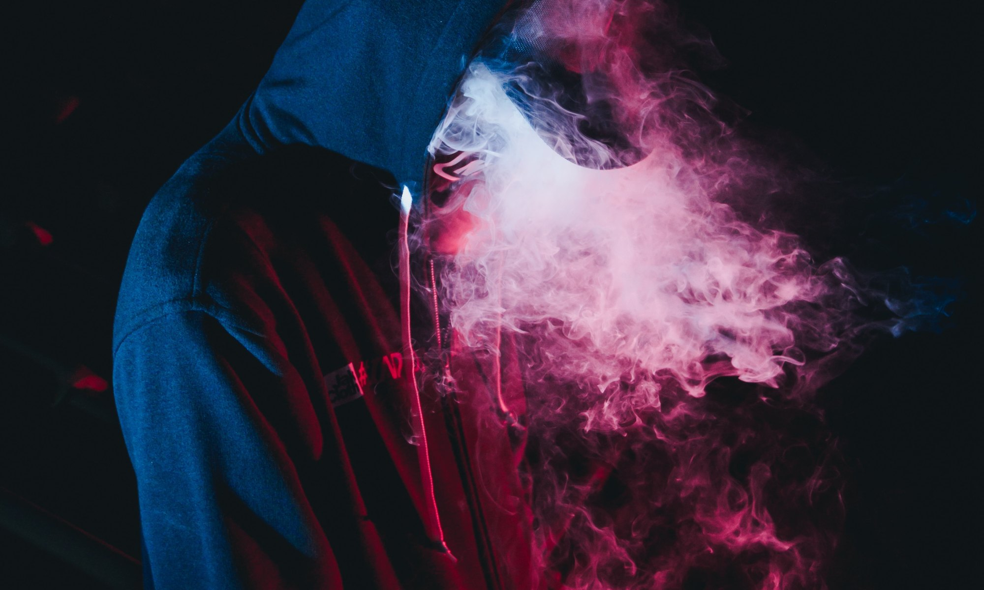 Person in black hoodie surrounded by smoke