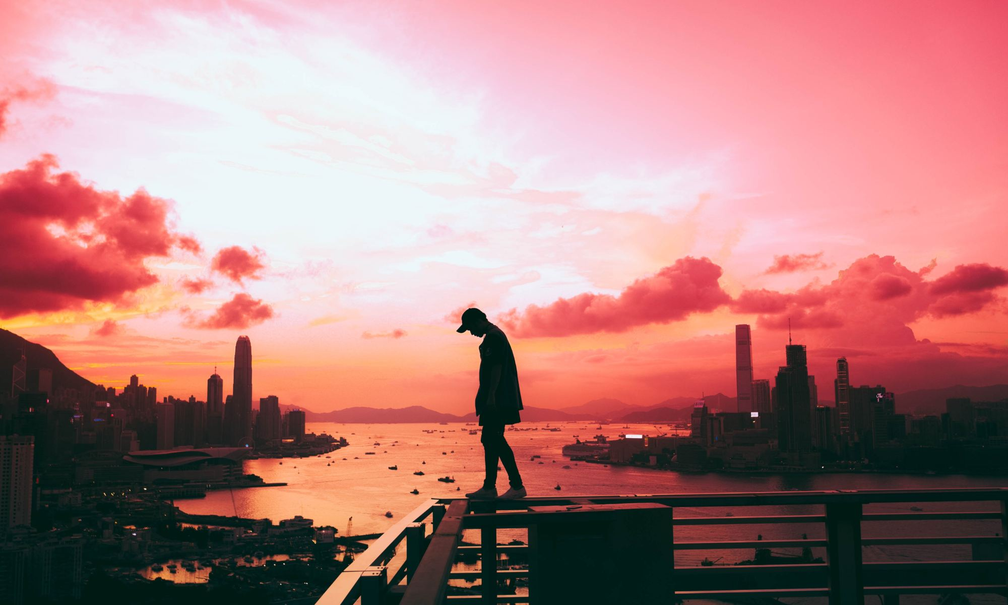 Silhouette of lonely person standing on railing