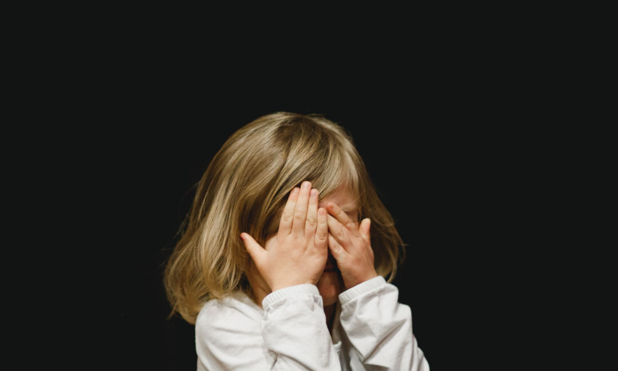Young girl scared of a pedophile and covering her face with both hands