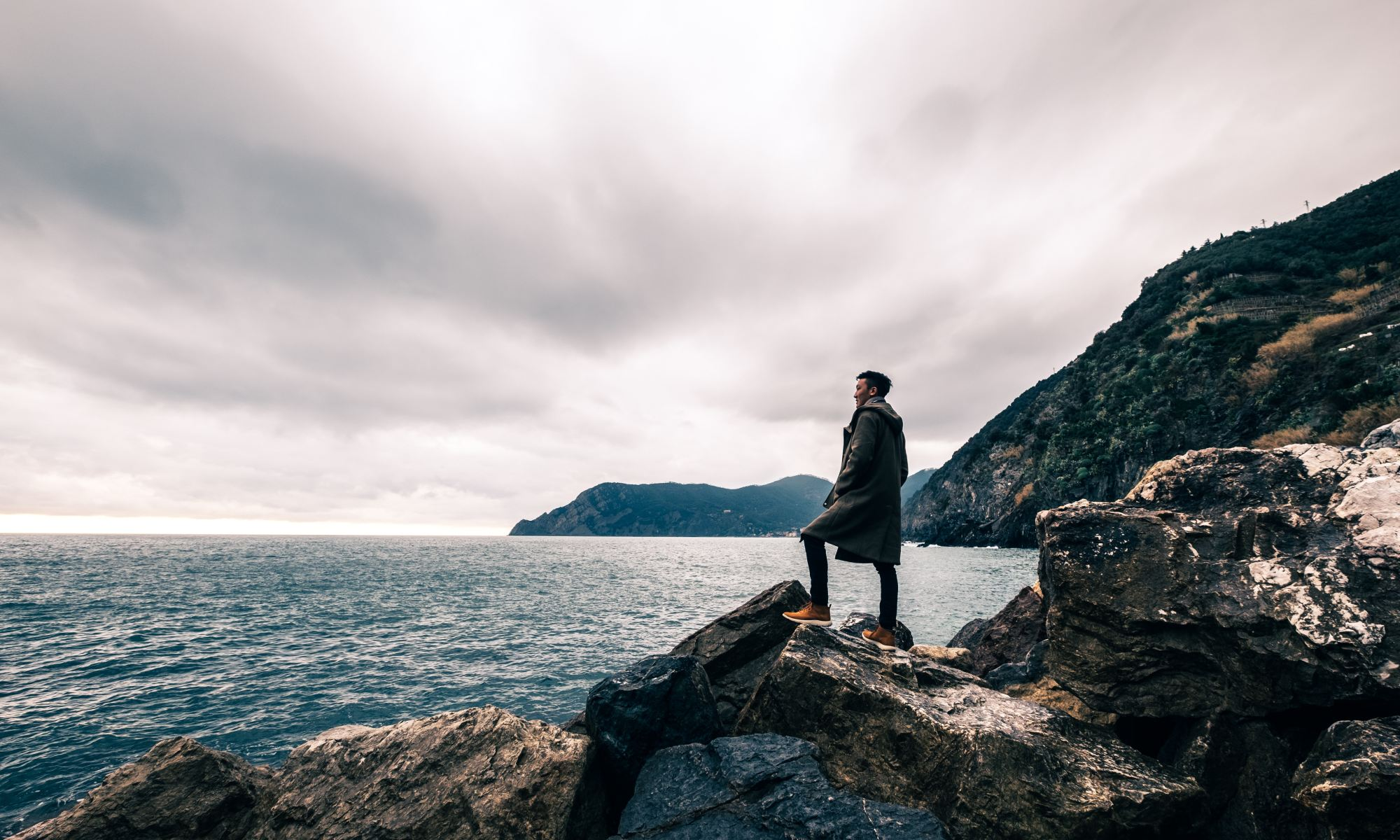 Motivated young man standing on boulder near body of water