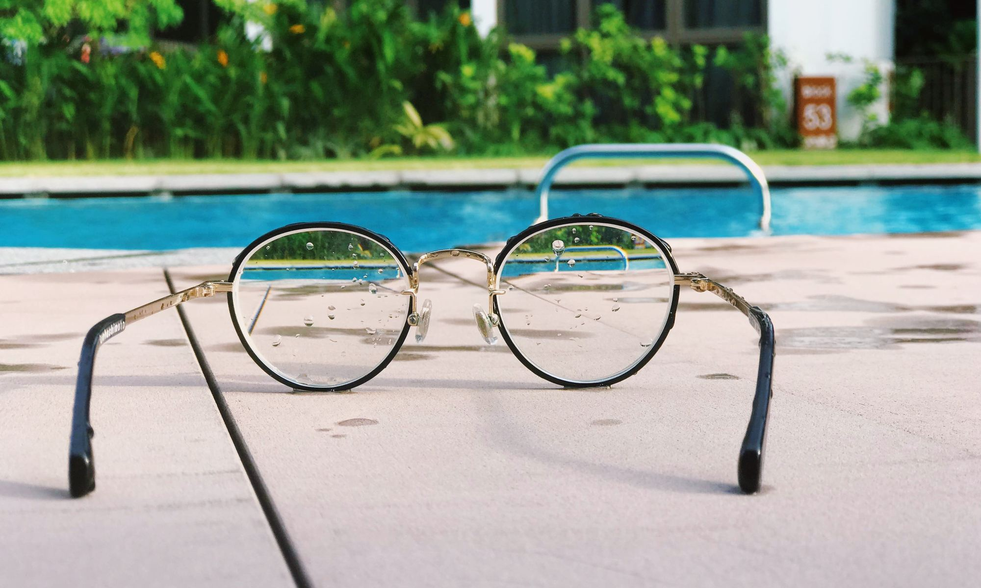 Eyeglasses with black frames on the ground by swimming pool