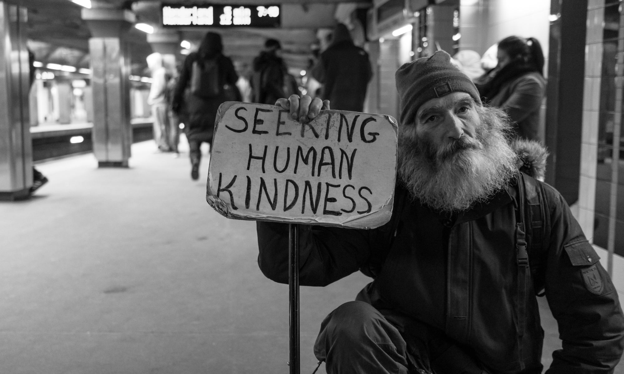 Homeless man in subway station holding card with seeking human kindness text