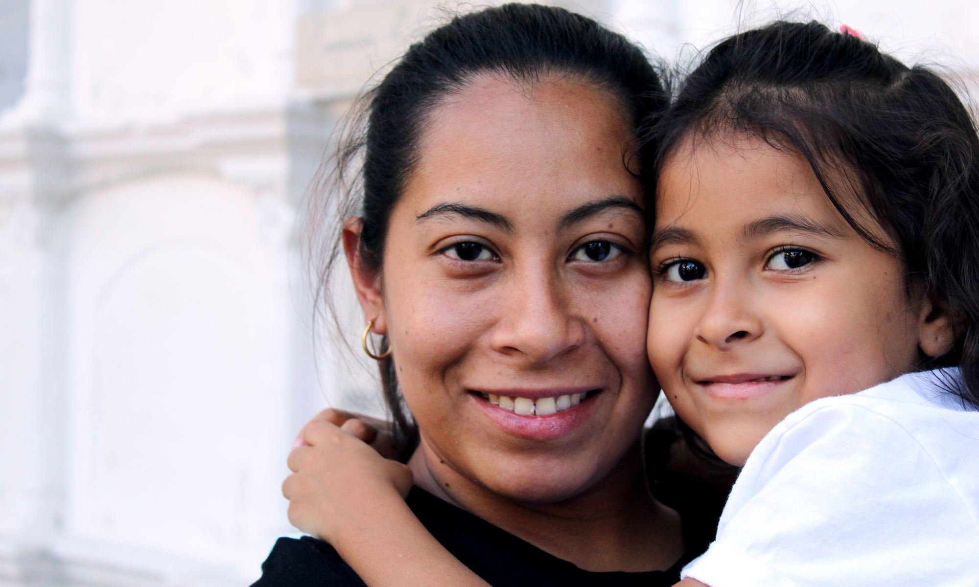 Hispanic immigrant mother holding daughter in her arms