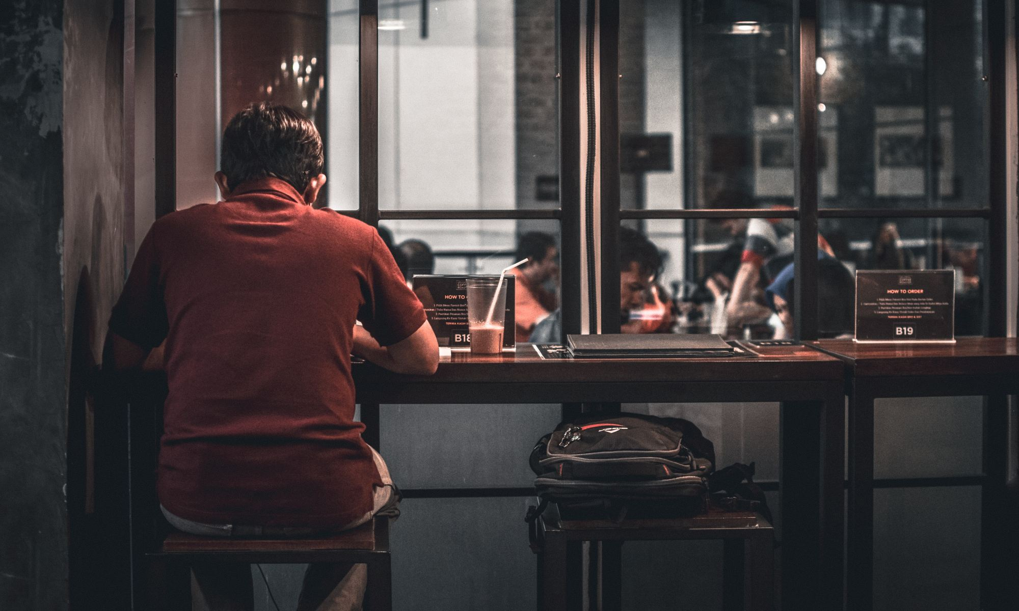 Lonely young man sitting alone on brown wooden bar stool