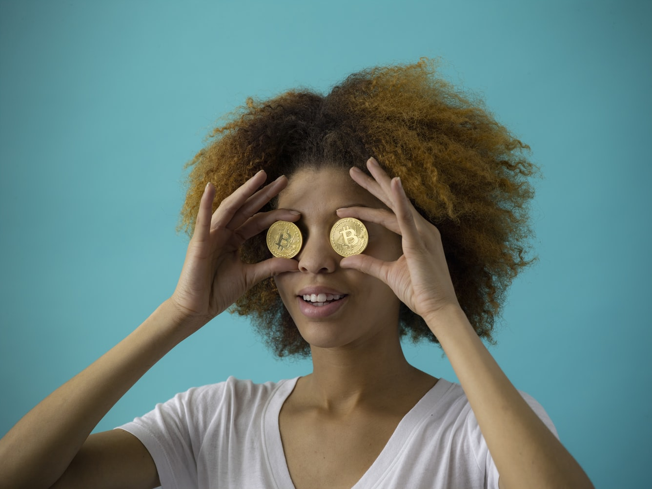 Black woman with an afro holding two bitcoins on her eyes