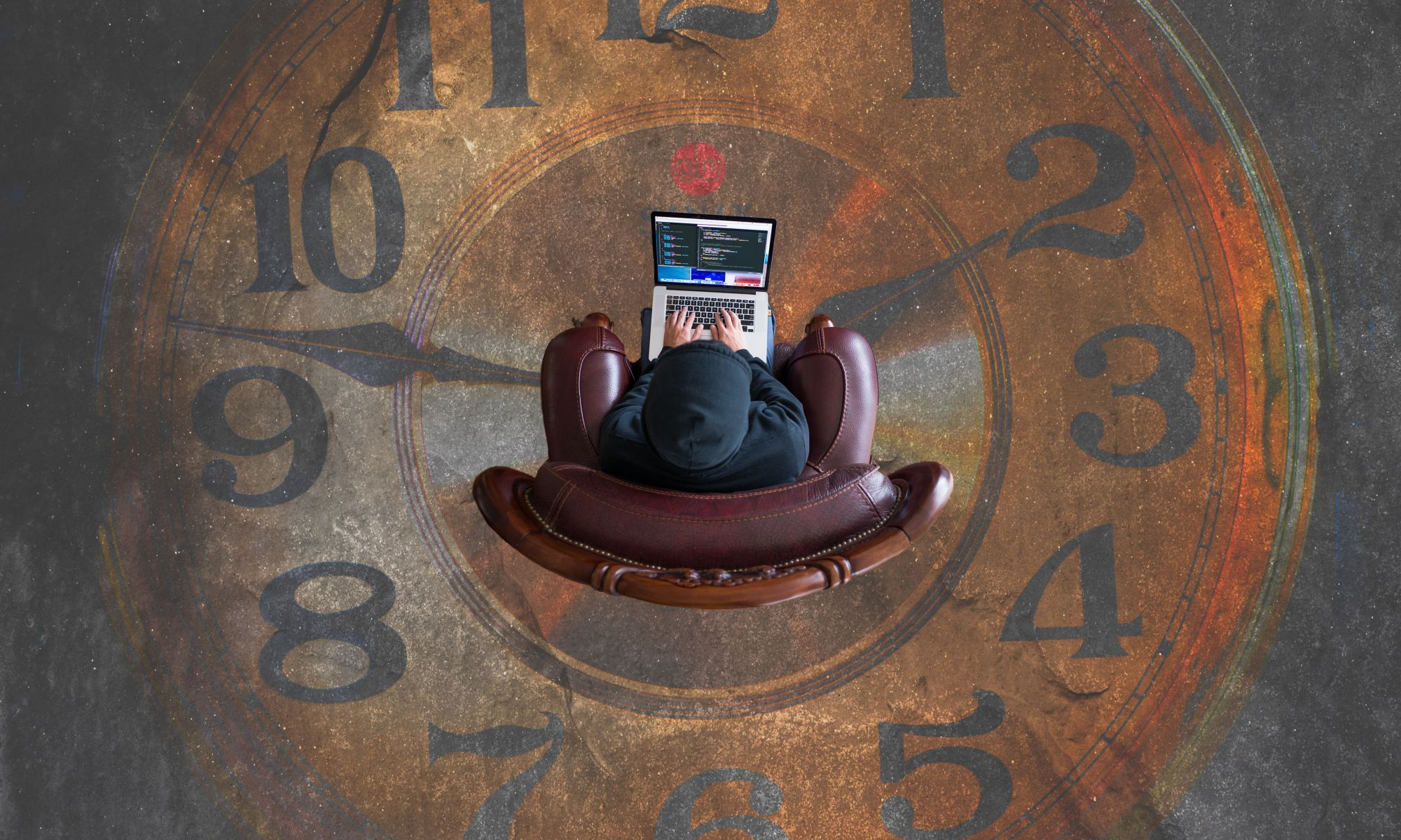 Person sitting on chair in the middle of a brown analog clock working on laptop
