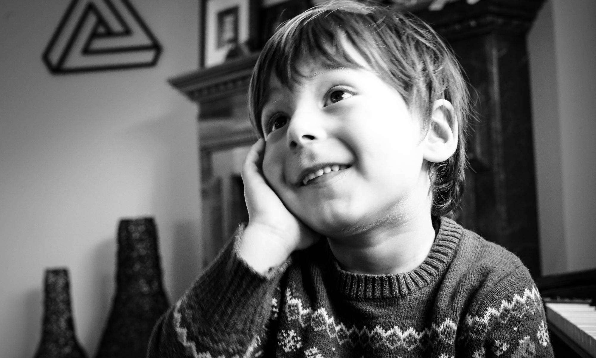 Smiling boy resting on his hand using his imagination