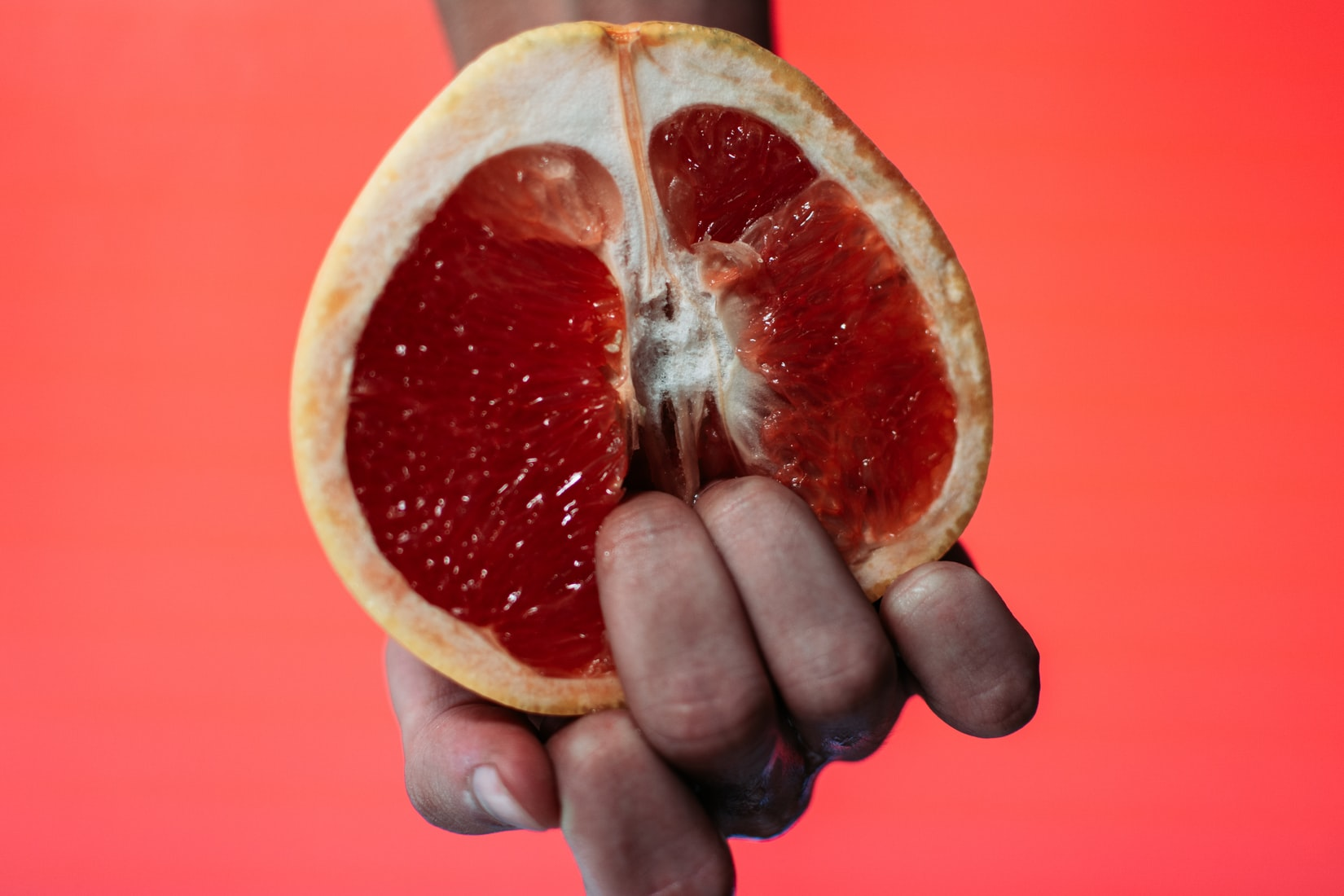 Man's fingers in a sliced red fruit
