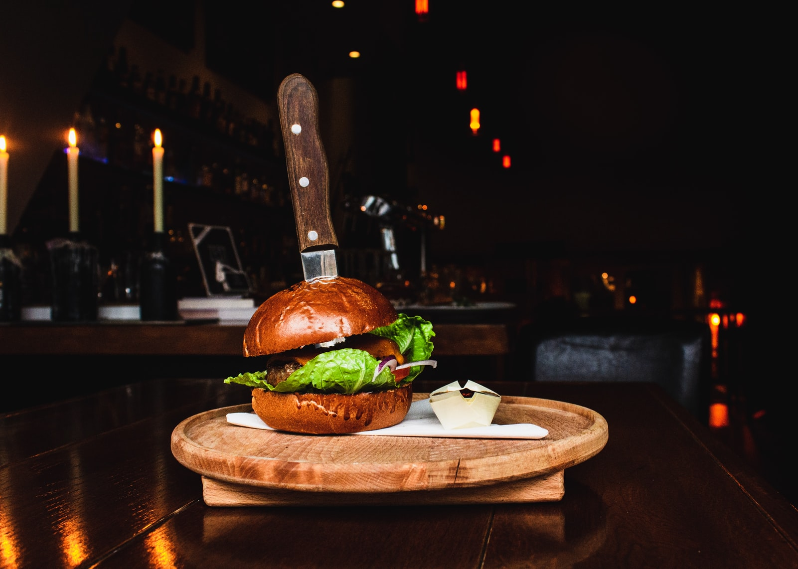 Selective focus photography of big burger with knife into it on brown wooden tray