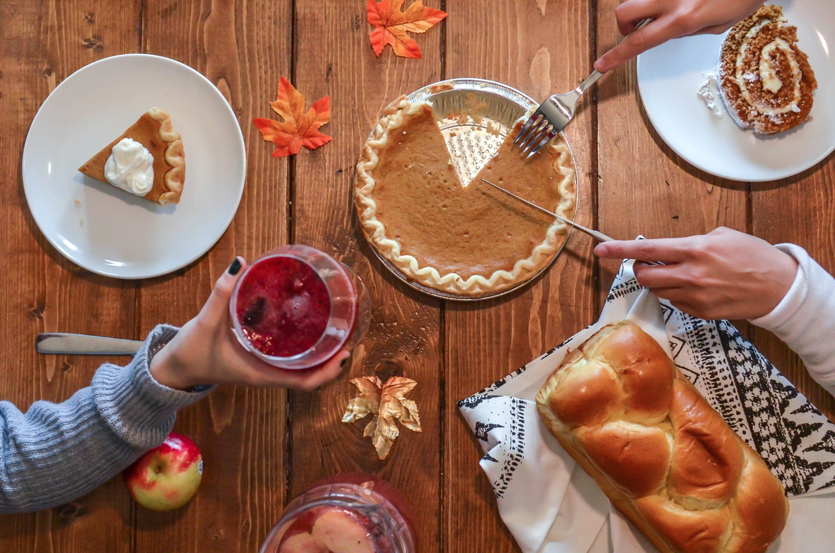 Two people enjoying pie and bread during Thanksgiving