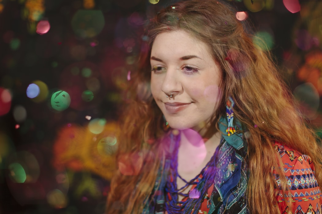 Bokeh photography of young woman experiencing colorful hallucinations