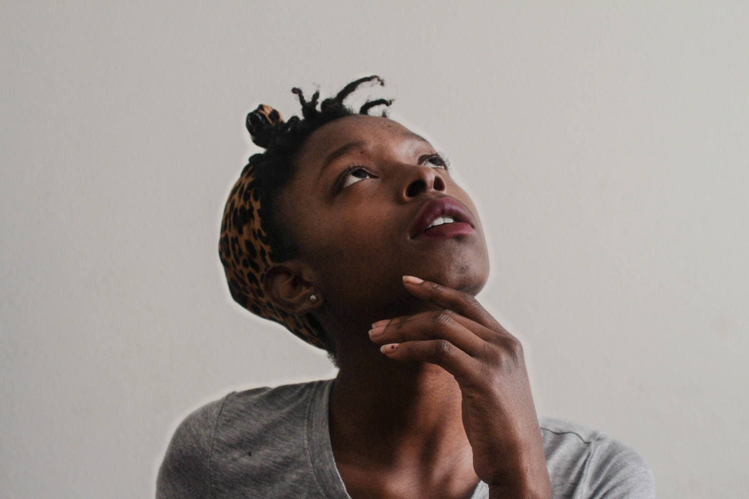 Black woman looking up and believing while holding hand on chin