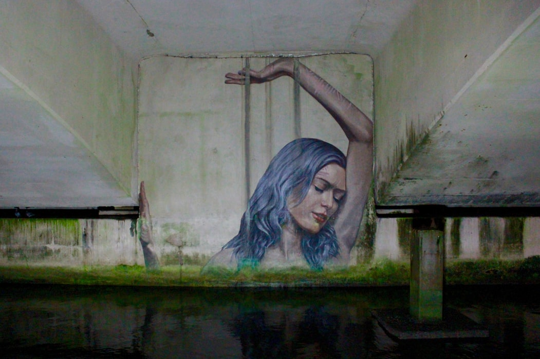 Graffiti of blue-haired woman suffering from karma on wall of underpass by sewage