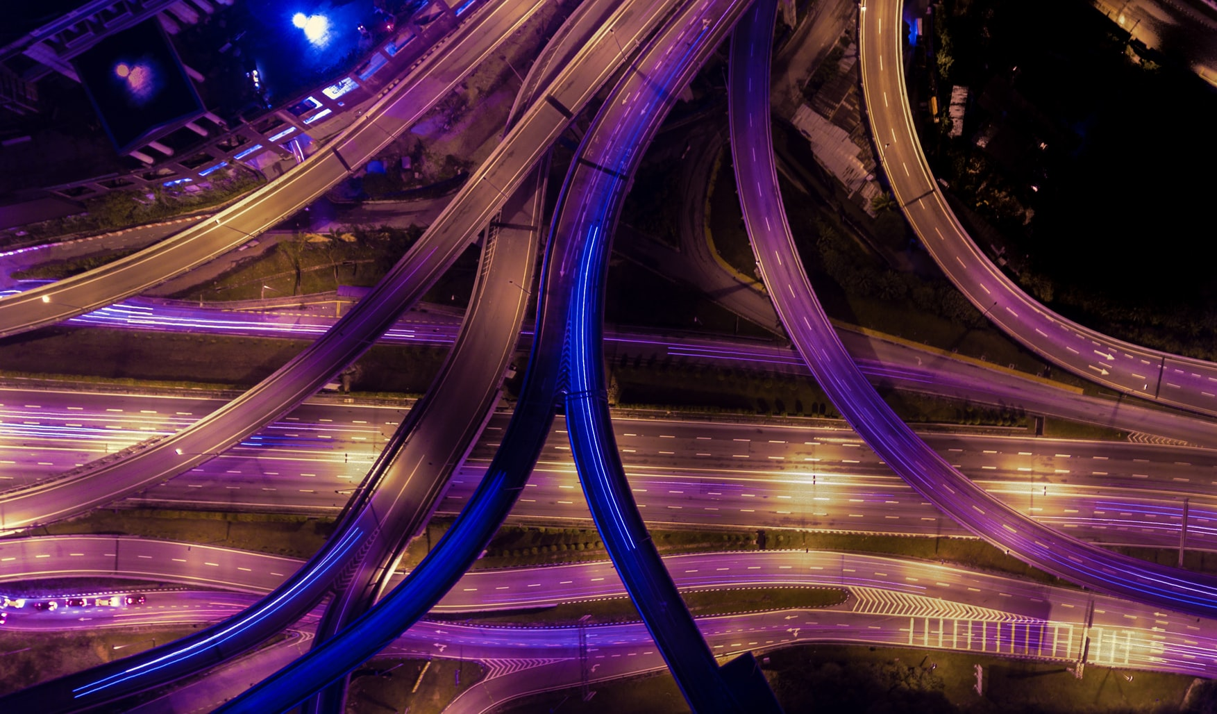 Aerial photography of colorful roads and highways merging during nighttime