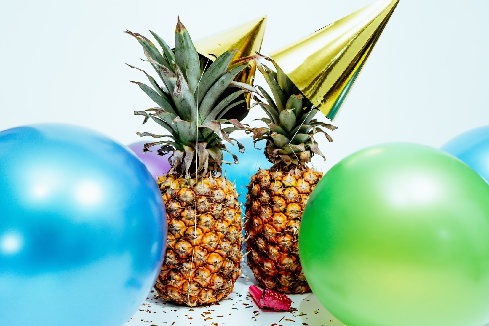 Two pineapples with gold party hats near blue and green balloons during the new year