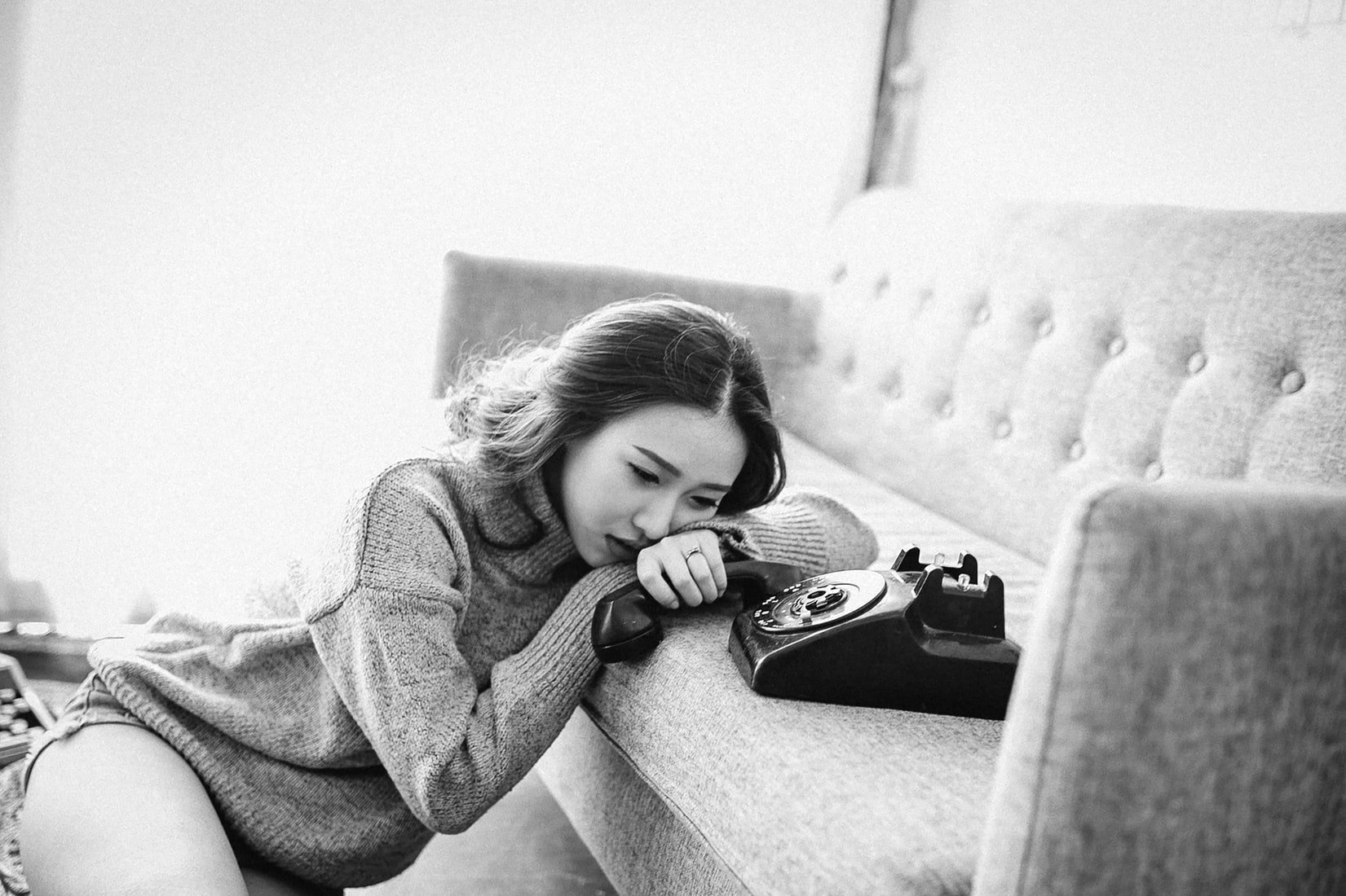 Depressed brunette asian woman leaning on sofa holding phone in hand