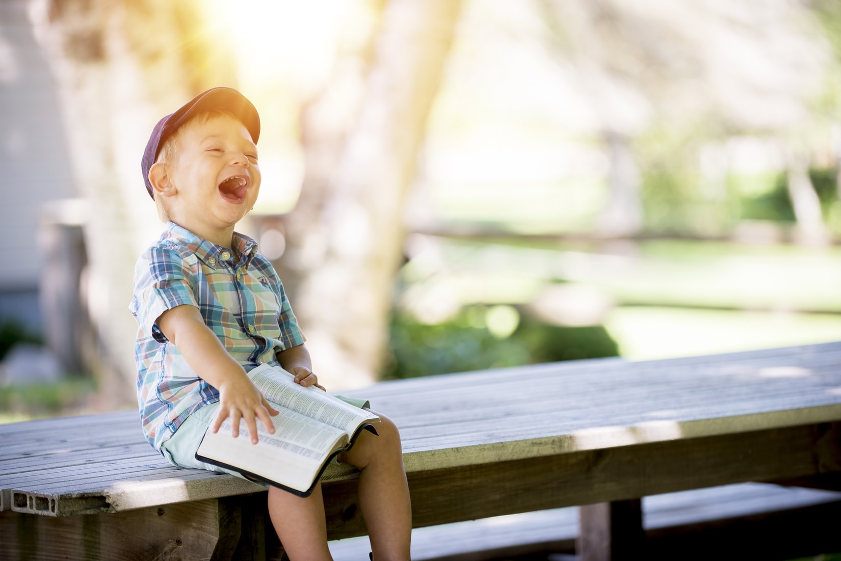 Boy sitting on bench and laughing while holding the bible