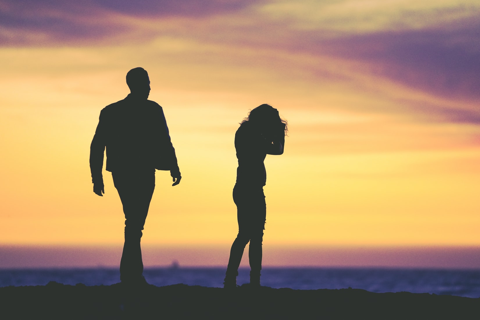 Silhouette of man and woman crying under yellow sky