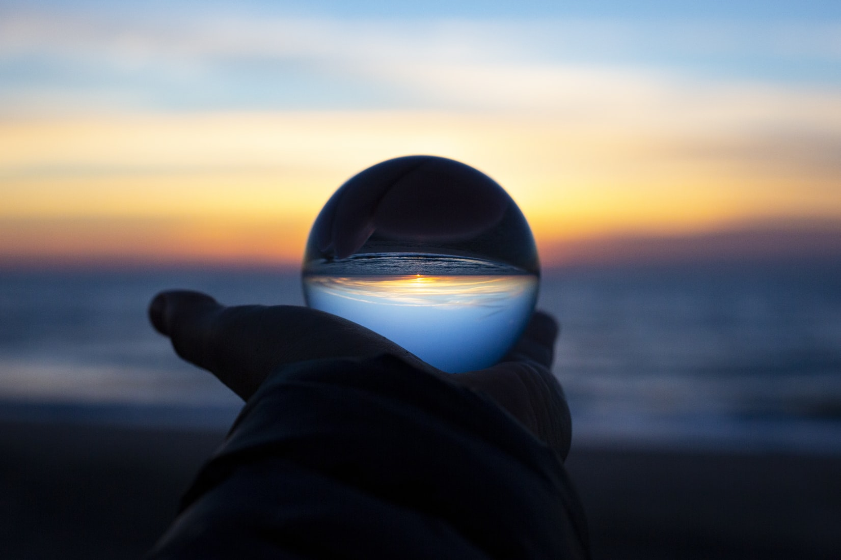 Person holding clear round glass in front of body of water