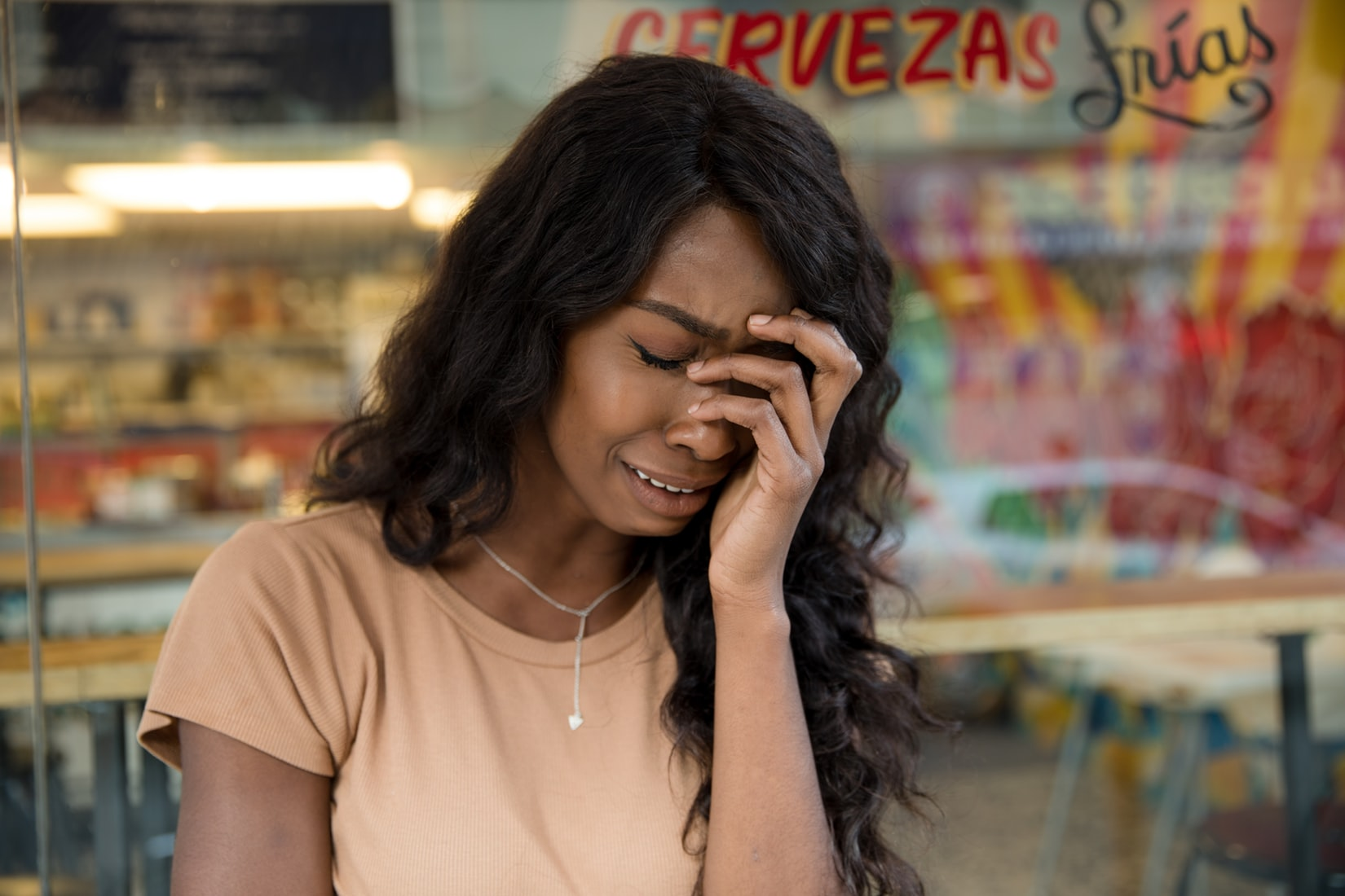 Sad black woman crying with hand on face