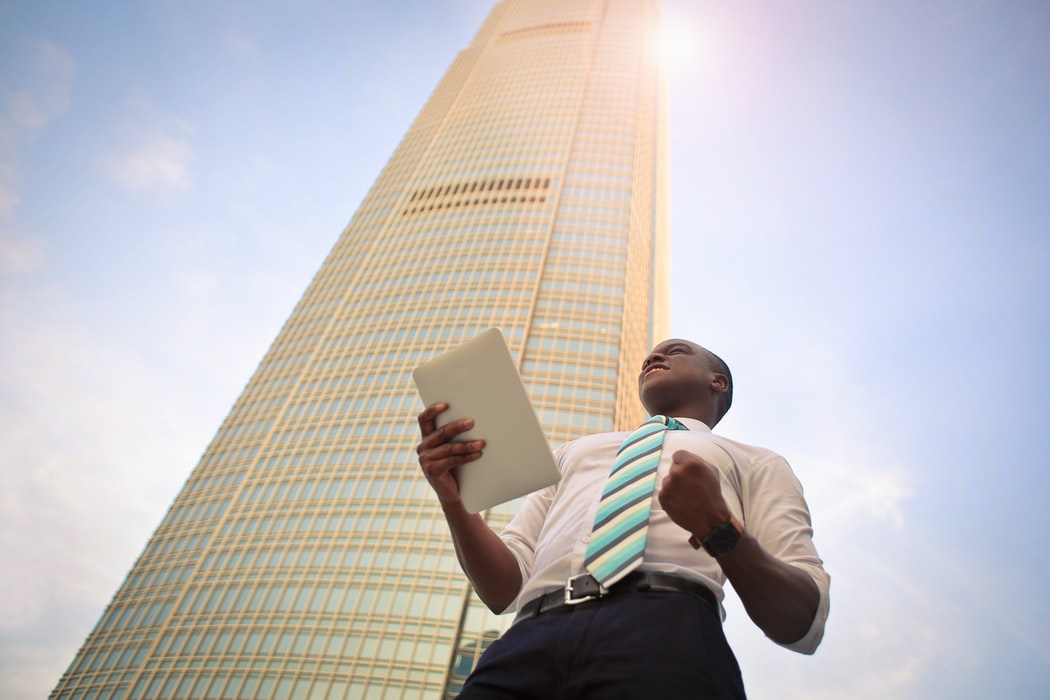 Motivated and hard-working black man doing a fist pump and standing next to high-rise building
