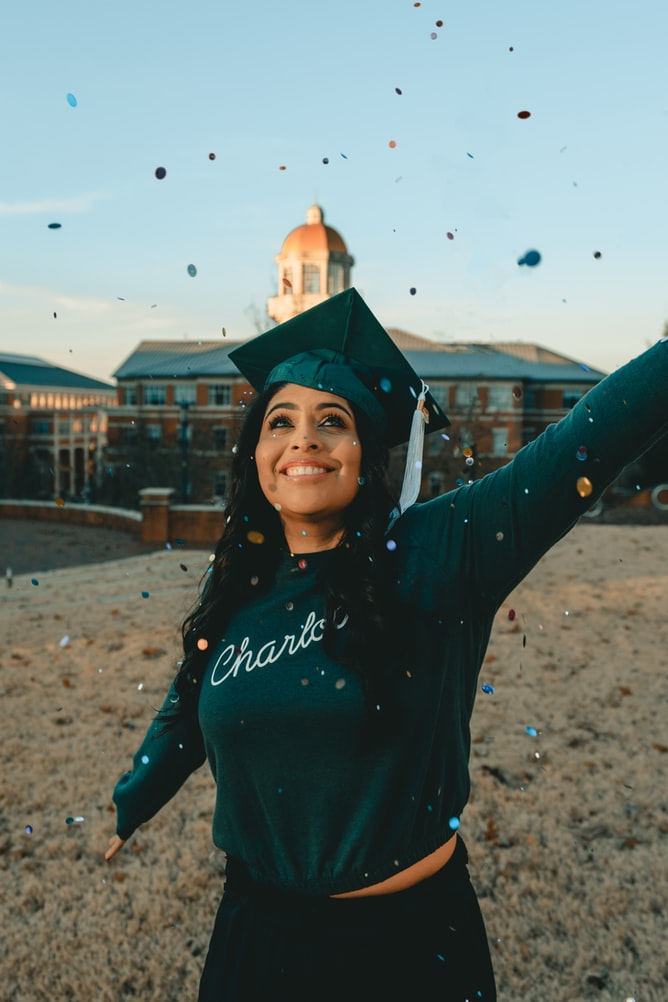Black woman with green graduation cap celebrating in front of university