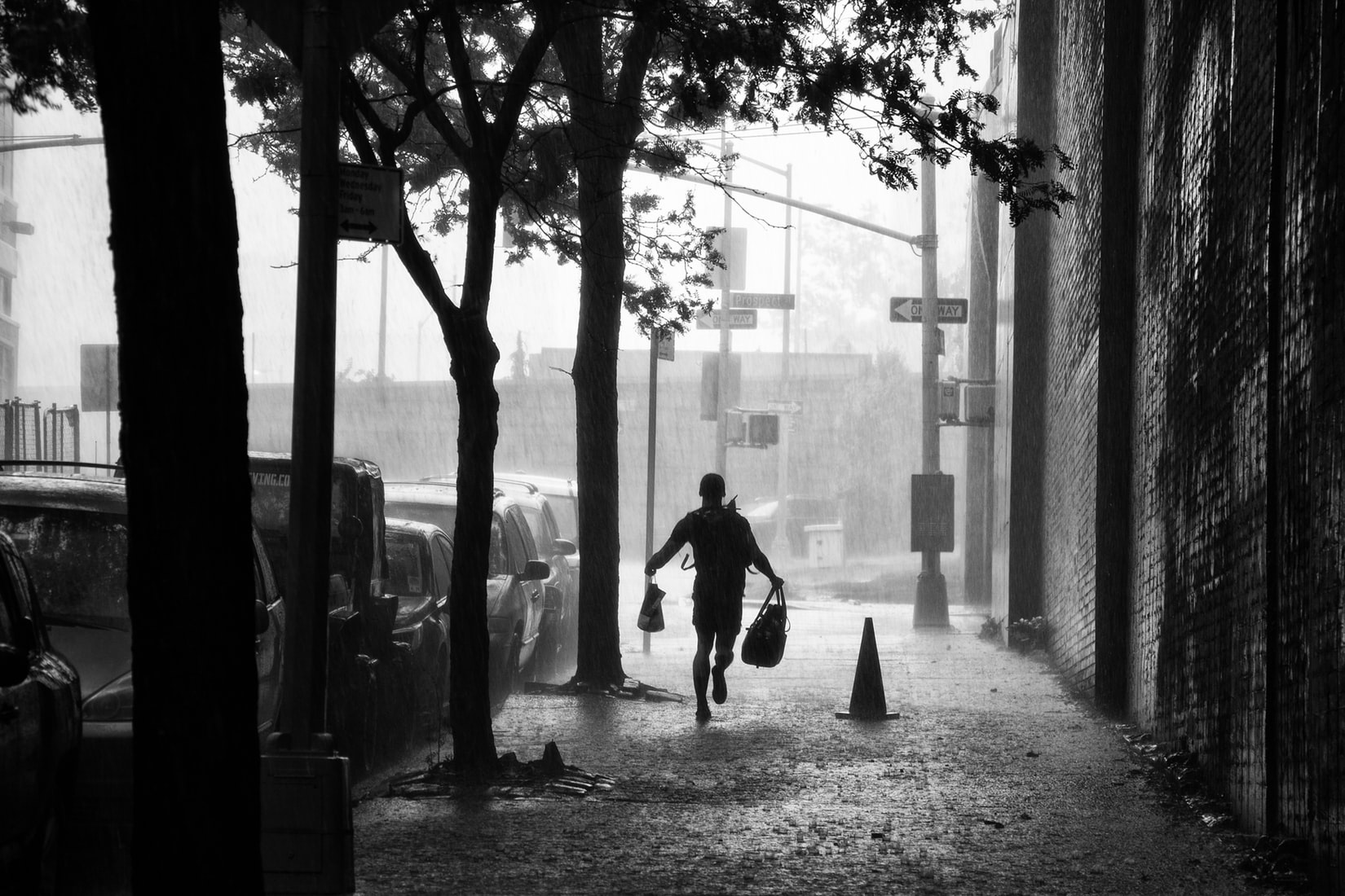 Man holding bags and running beside building on sidewalk