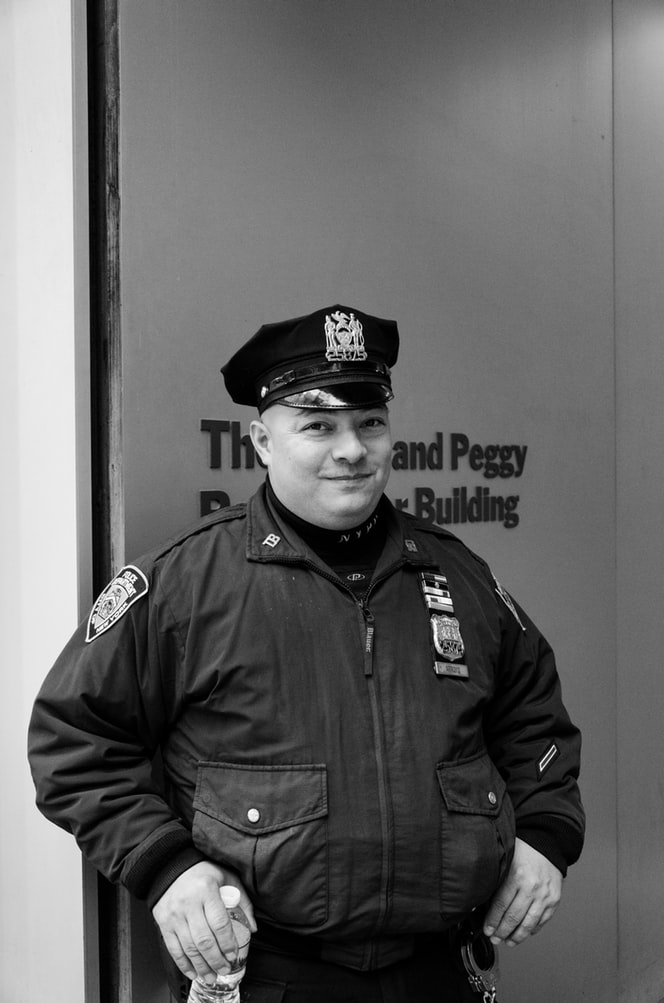 Grayscale photography of white police officer holding water bottle