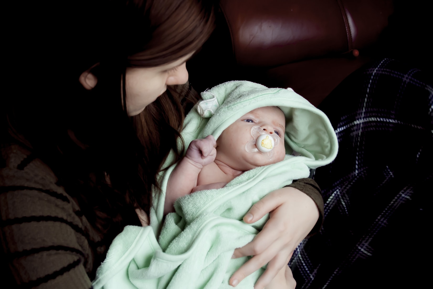 Mother with postpartum depression holding baby in her arms