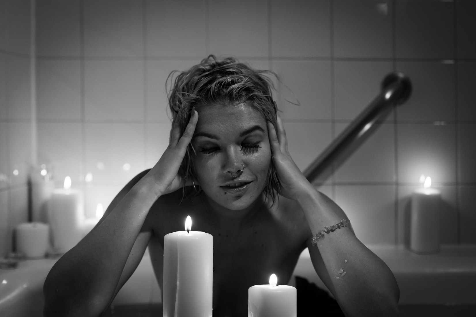 Grayscale photography of woman in bathtub in front of white burning candles