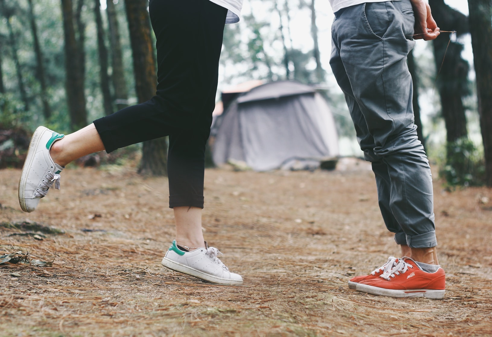 Woman standing in front of man near tent in woods