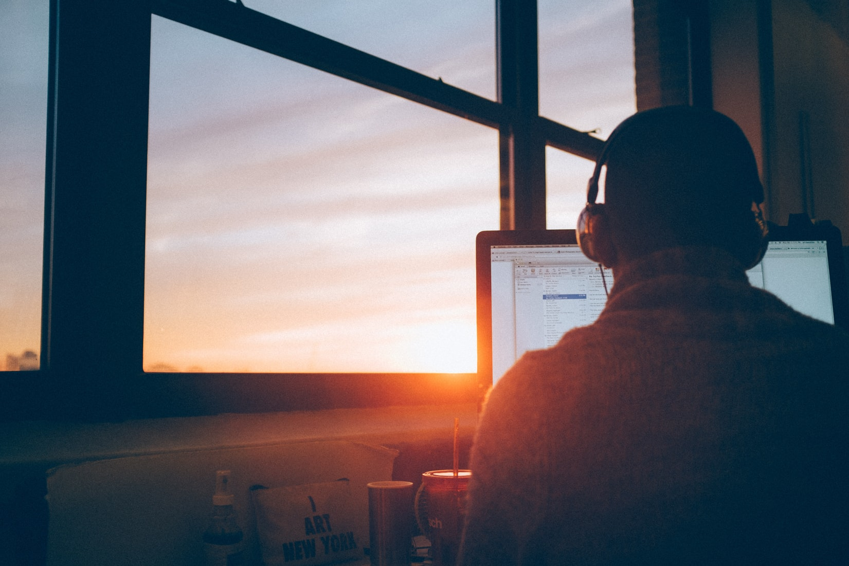 Man with headphones on working on computer near large window